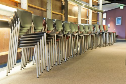 Chairs in an office stacked and lined up prior to a corporate meeting.